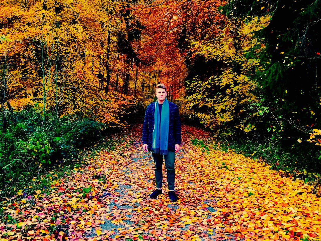 autumn, change, leaf, full length, one person, real people, tree, front view, nature, looking at camera, forest, standing, day, outdoors, lifestyles, portrait, casual clothing, trousers, leisure activity, red, young adult, park - man made space, smiling, beauty in nature, young women, adult, people