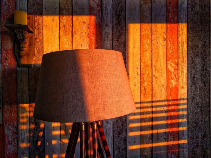 Close-up of electric lamp against wooden wall