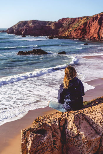 Sea Beach Rock Sitting Lifestyles Portugal Algarve Sunset Evening Romantic Meditation Looking At View Women Girl Dreaming Thinking No Face One Person Alone Single Sad Waiting Waves Rear View Nature
