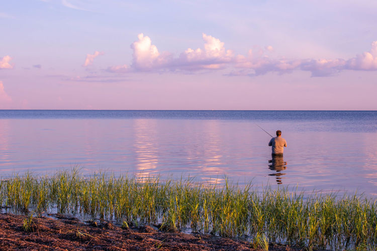 Man standing in sea against sky during sunset