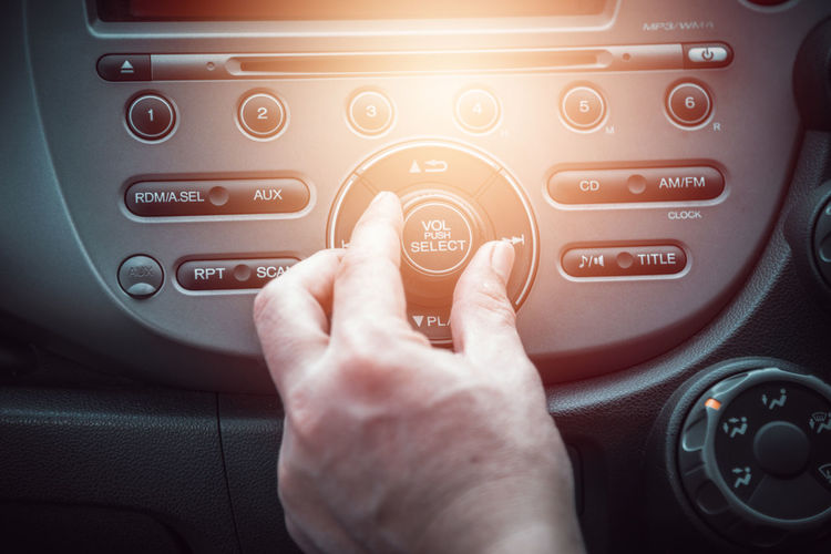 Cropped hand of man playing music in car