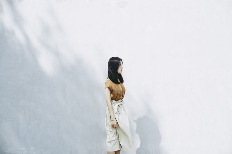 Woman standing against white wall