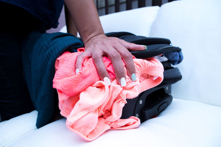 Midsection Of Woman Packing Overburdened Bag On Sofa