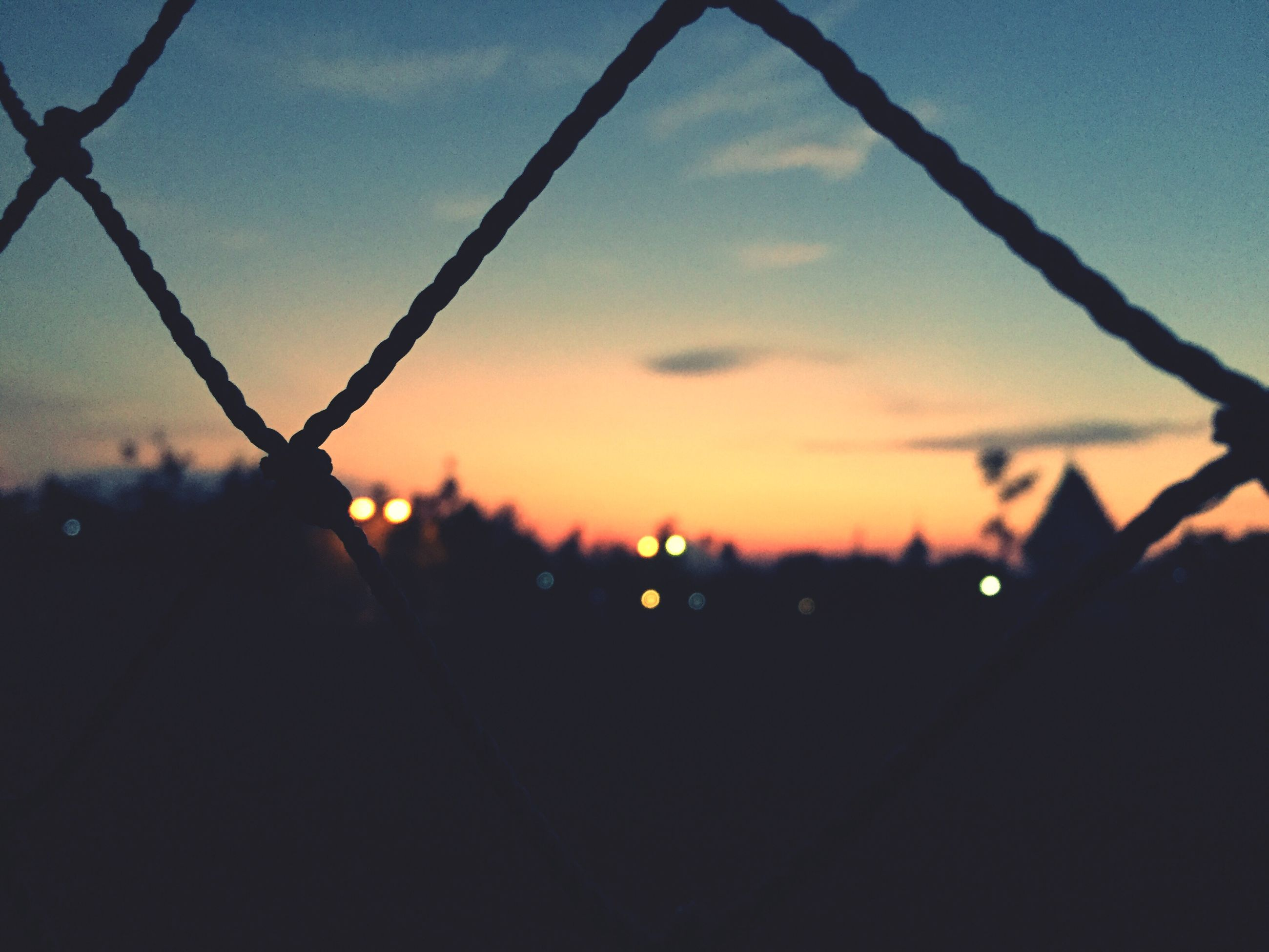 sunset, sky, silhouette, focus on foreground, close-up, fence, nature, orange color, dusk, beauty in nature, sun, protection, no people, safety, metal, tranquility, outdoors, sunlight, chainlink fence, scenics