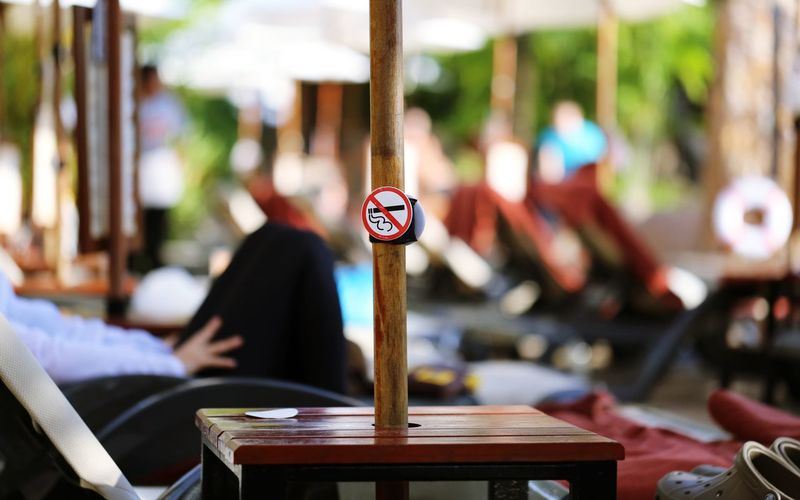 Hanging Out No Smoking In Puplic Smoke Smoking Travel Vacations Chair Close-up Day No Smoking No Smoking Area No Smoking Sign No Smoking Signs Outdoors Seat Selective Focus Sign Sitting Sunset Swimming Pool Table Text Tropical Wood - Material