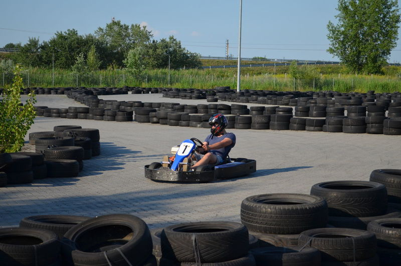 Man driving go-cart amidst tires on street