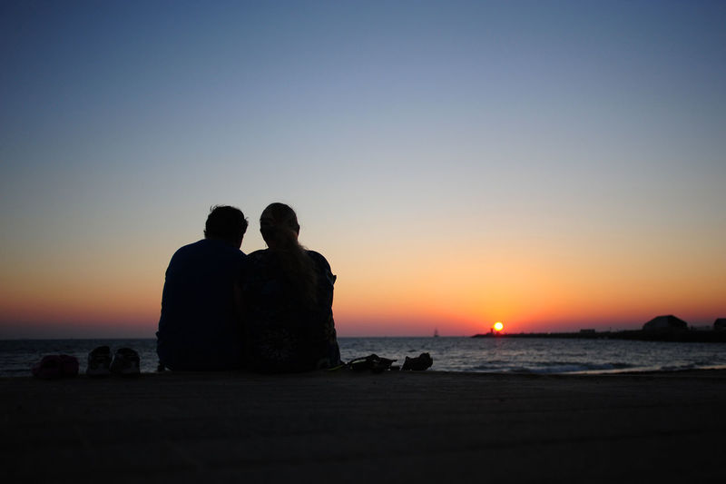 Silhouette Couple Sitting On Promenade Against Sky During Sunset