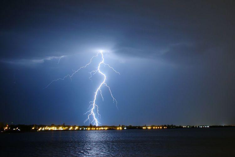 Lightning over lake at night