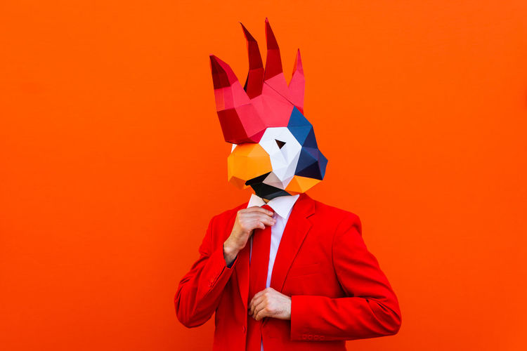 Person wearing mask against orange background