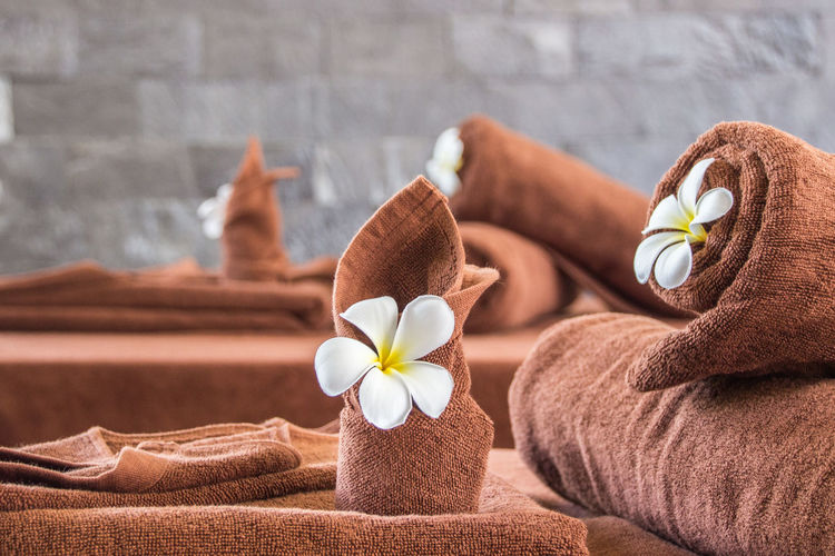 Close-up of towels and flowers on massage table in spa room Beauty In Nature Beauty Spa Body Care Brown Close-up Flower Flowering Plant Food Food And Drink Frangipani Freshness Health Spa Healthy Lifestyle Human Body Part Indoors  Indulgence Luxury Relaxation Spa Treatment Still Life Towel Wellbeing