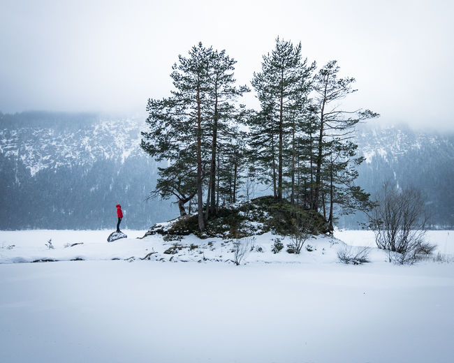 Frozen Eibsee in Winter Eibsee Frozen Lake Zugspitze Adventure Beauty In Nature Cold Temperature Day Full Length Landscape Lifestyles Mountain Nature One Person Outdoors People Real People Scenics Sky Snow Tranquil Scene Tranquility Tree Vacations Weather Winter