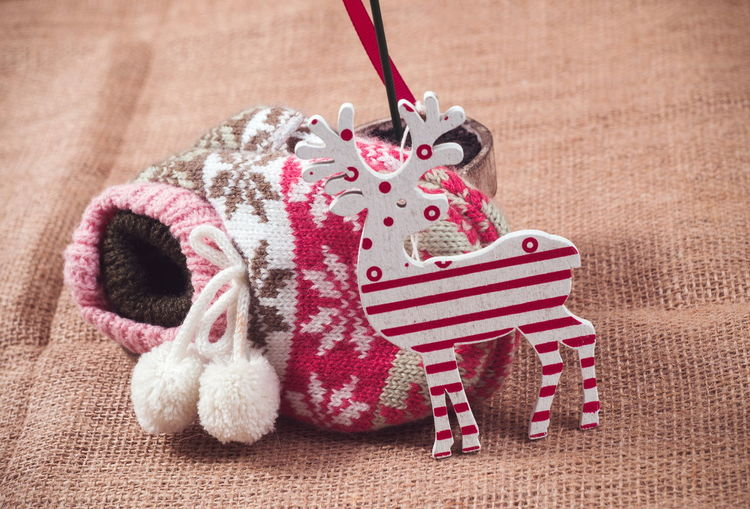 Close-Up Of Christmas Decoration And Knit Hat On Textile