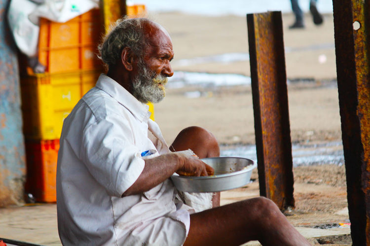 Man eating food while sitting outdoors