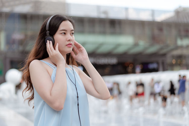 Woman looking away while standing on mobile phone