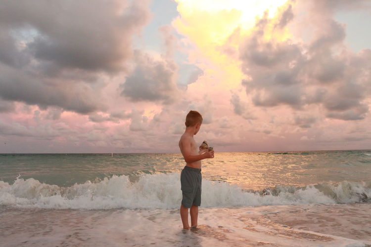 Boy standing on beach during sunset