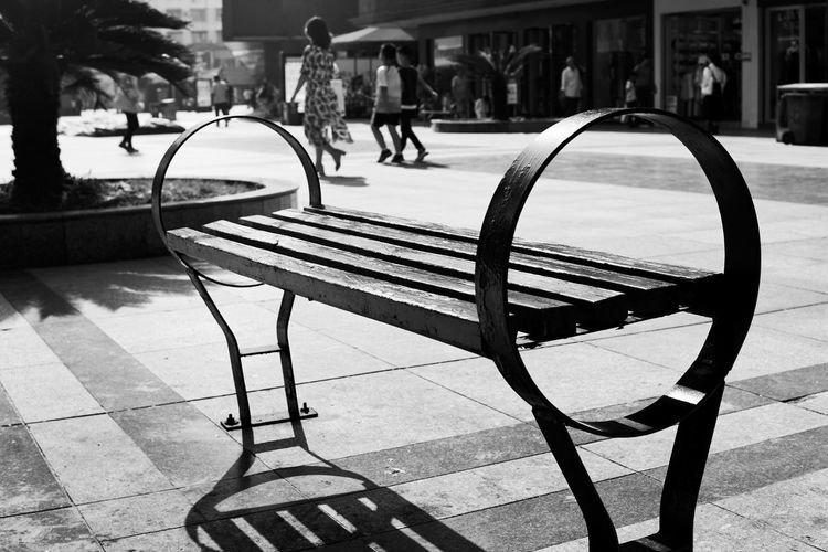 Empty park bench by street in city
