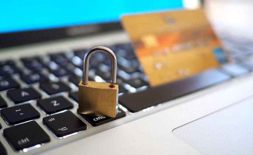 Close-up of padlock and credit card on keyboard