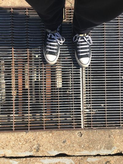 Low section of person standing on metal grate