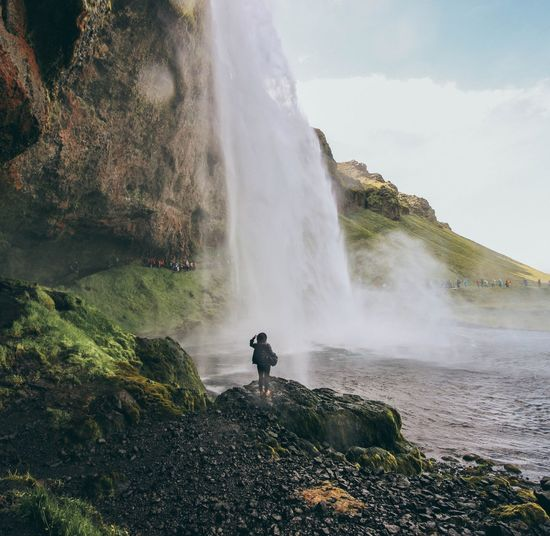 Woman looking at waterfall against sky