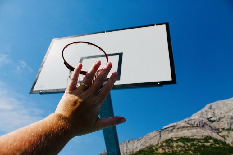 Low angle view of person hand against basketball hoop and blue sky