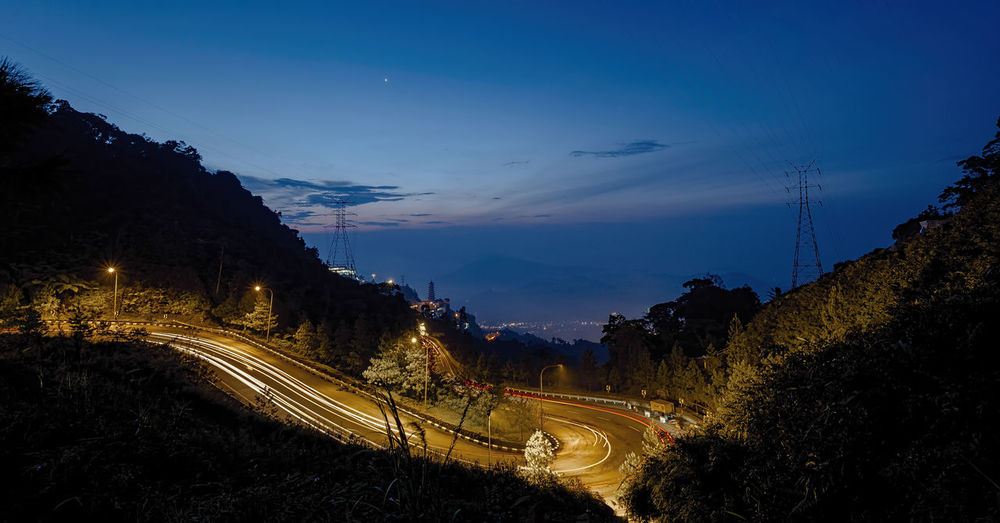 Down hill Genting Highland light trail with Chin Swee Caves Temple and Cable cars at the distance during blue hour Beauty In Nature Cloud - Sky Dusk Illuminated Light Trail Long Exposure Mode Of Transportation Motion Mountain Nature Night No People Outdoors Plant Road Scenics - Nature Sky Speed Street Transportation Tree