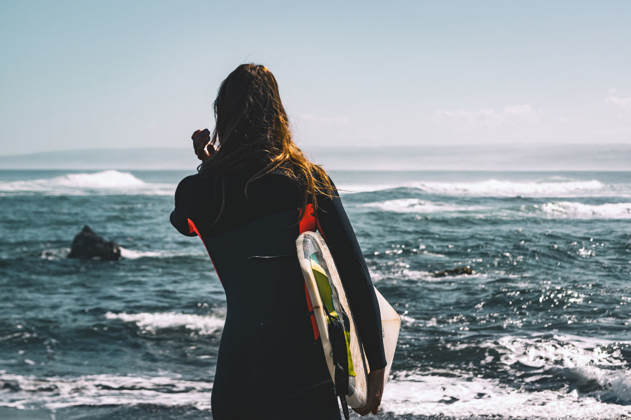 sea, rear view, real people, horizon over water, standing, sky, one person, water, nature, lifestyles, leisure activity, beauty in nature, scenics, wave, women, sunlight, outdoors, beach, day, vacations, men, adult, people