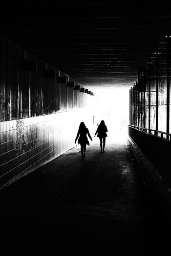 Rear view of silhouette people walking on footpath in tunnel