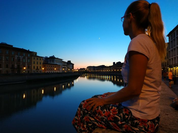 Side view of woman sitting by canal in city against sky