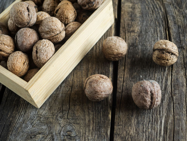 walnuts in a wooden box on an old weathered wooden table Box Weathered Wood Background Close-up Day Directly Above Directly Abowe Food And Drink Freshness High Angel View High Angle View Indoors  No People Old Table Walnuts Wood - Material Wooden