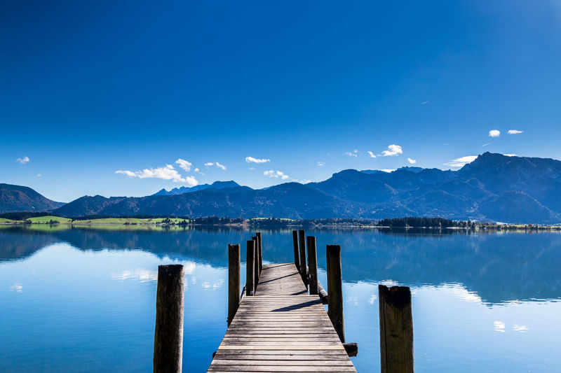 Wooden jetty on pier over lake against blue sky