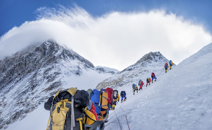 Panoramic view of people on snowcapped mountains against sky