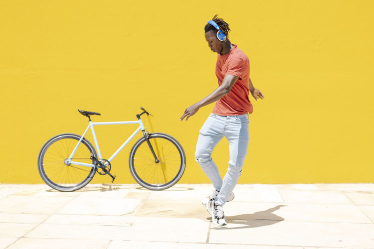 Full length of man riding bicycle against yellow wall