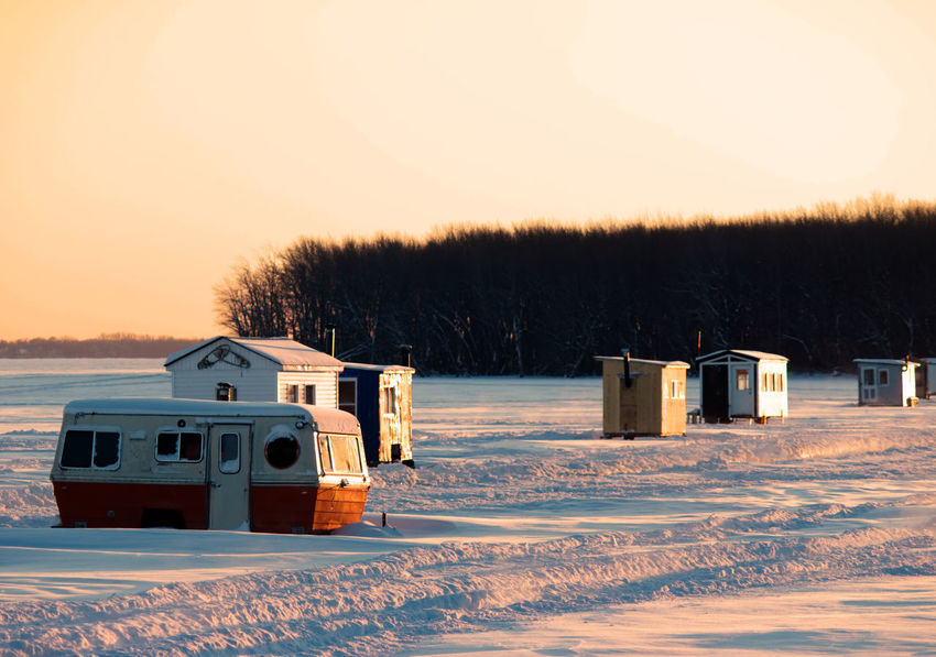 Ice fishing huts on a frozen lake at sunset Ice Fishing Beauty In Nature Cold Temperature Day Ice Fishing Huts Ice Fishing Huts On Frozen Lake At Sunset Landscape Nature No People Outdoors Scenics Sky Snow Sunset Tranquility Transportation Tree Winter