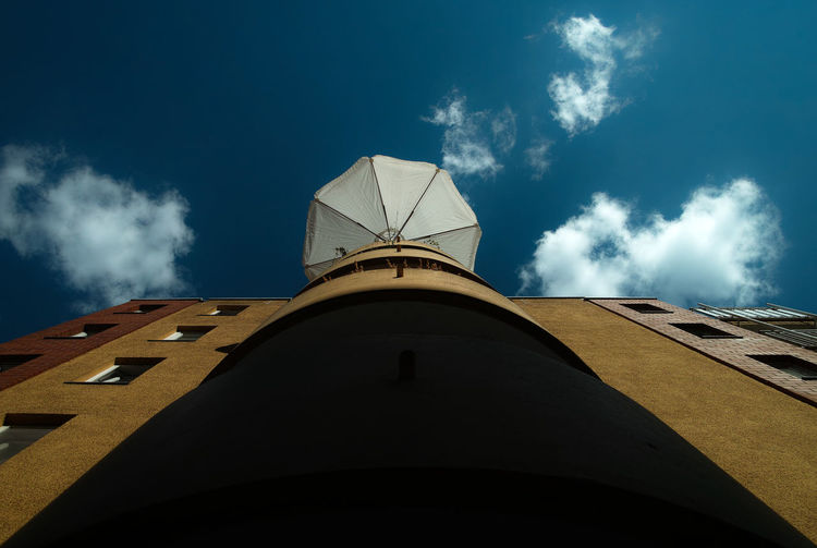 Low angle view of parasol on building against sky