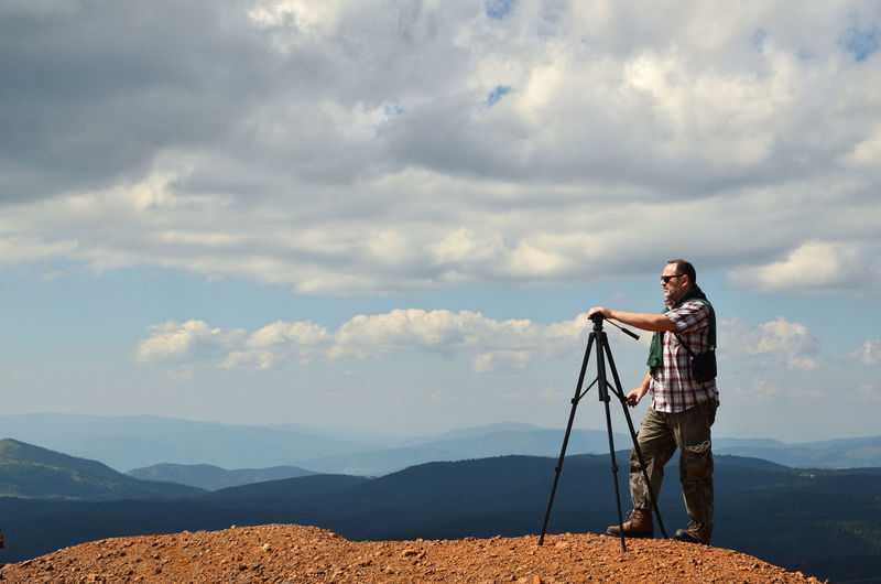 Man standing on mountain high preparing to shoot a wonderful landscape