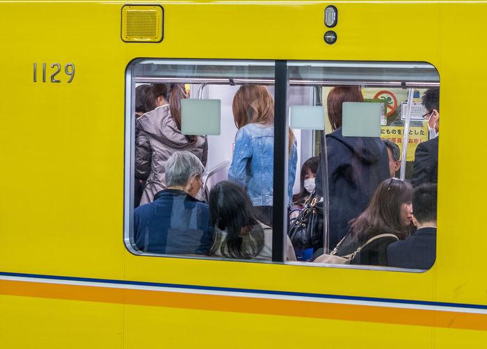 People In Yellow Train Seen Through Window