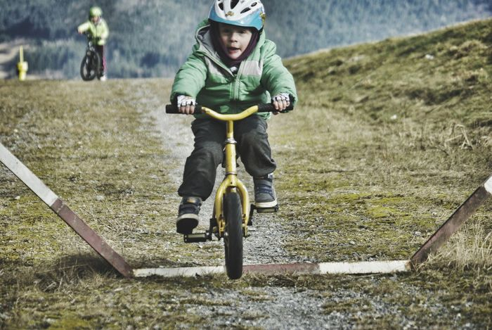 Kids Bike Bicycling Kids Sports Pictures Children Only Full Length Child Childhood Boy On Bike Looking At Camera Overcome The Fear Obstacles Movement Action Shot  Helmet Yellow Bike Preschool Age Excitement Adventure Happines Jump Crosscountry Speeding