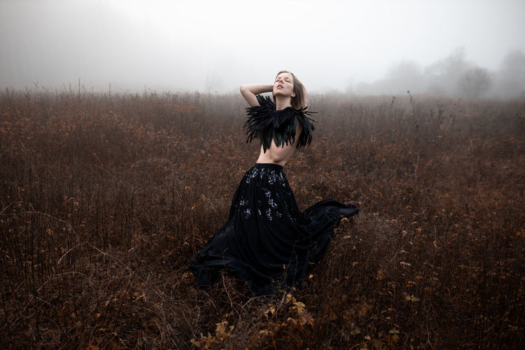 Woman standing on field during foggy weather