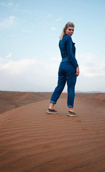 Full length of woman standing in desert