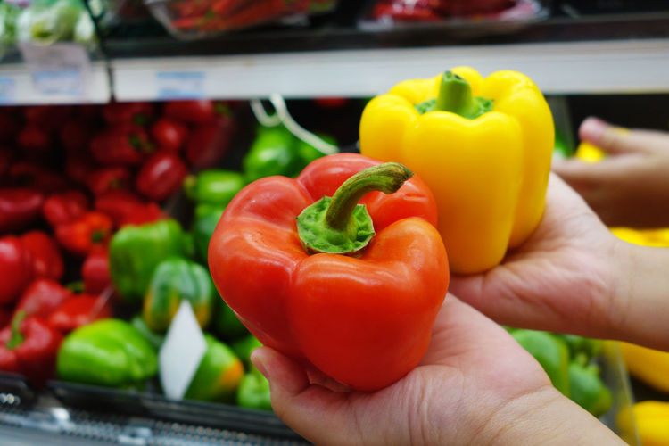 Cropped Image Of People Holding Bell Peppers At Market