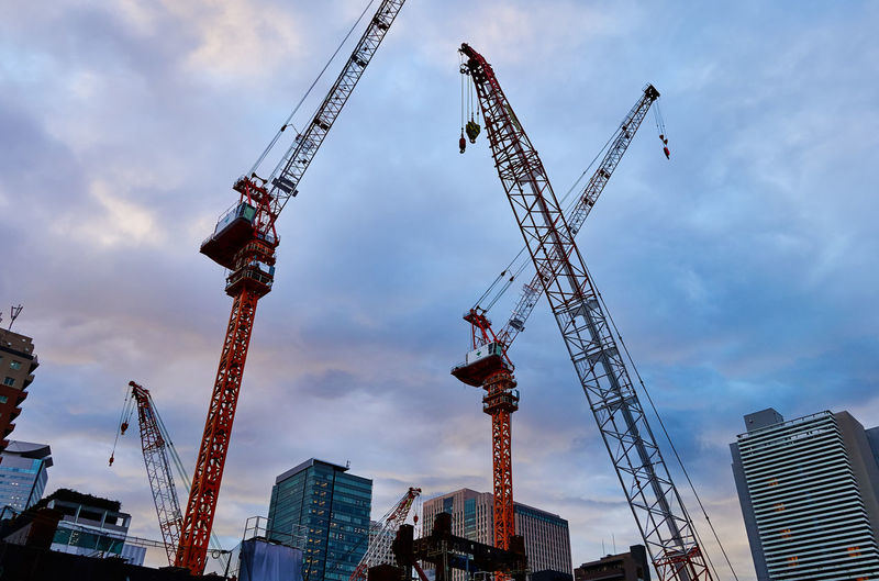 Low angle view of  construction cranes against sky in city