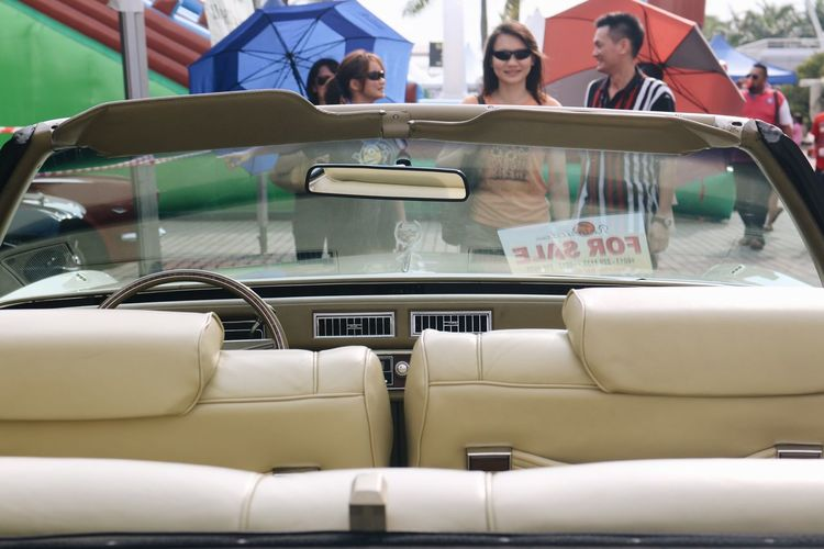 People Standing In Front Of Convertible Car For Sale