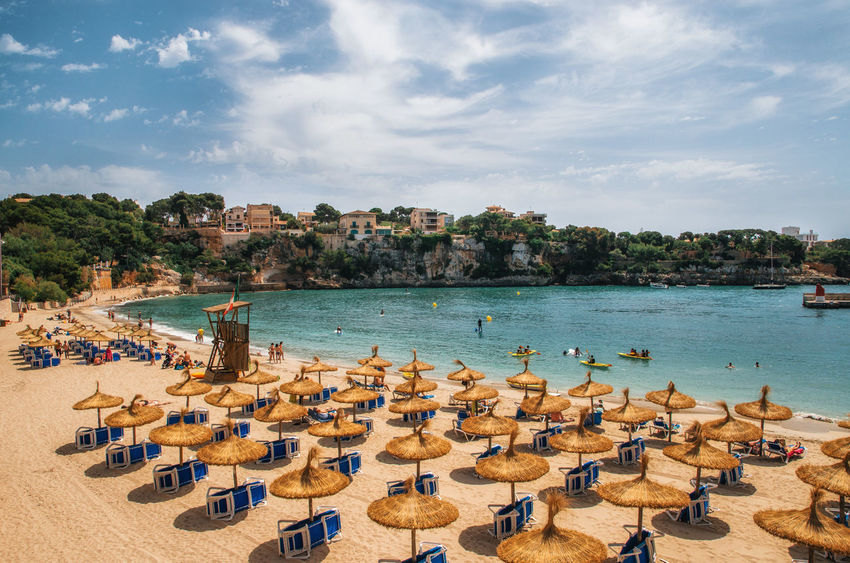 Straw umbrellas on the beach in Porto Cristo on Mallorca, Balearic Islands, Spain Abundance Baleares Bay Beach Beachphotography Europe Harbour In A Row Large Group Of Objects Majorca Mallorca Porto Cristo Sea Seaside Shore SPAIN Straw Sunbeds And Umbrella Sunshade Tourism Tourist Vacations Water
