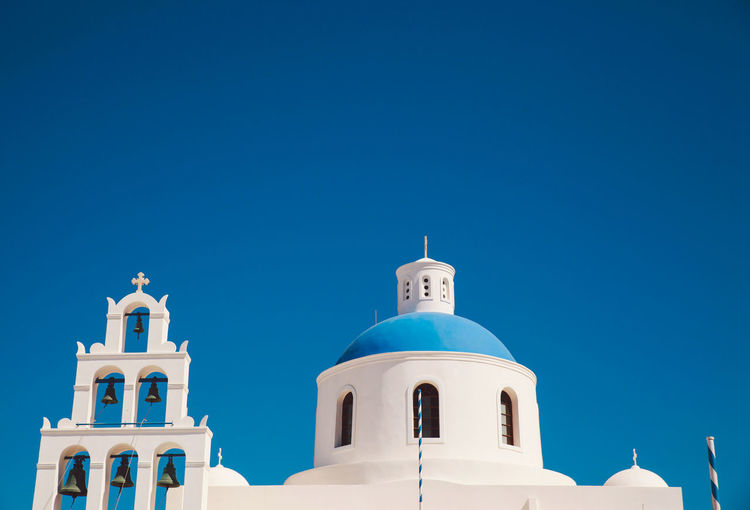 Low angle view of church at santorini against clear sky