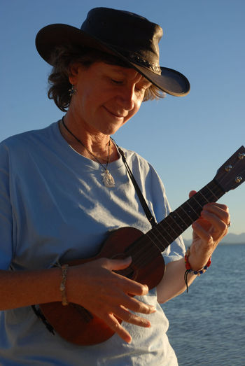 Low angle view of woman playing ukulele at beach