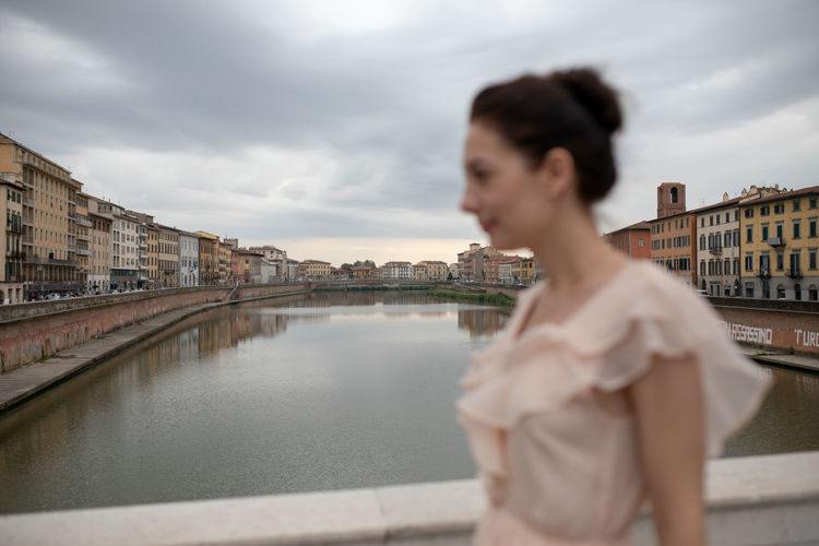 Side view of woman standing against river in city