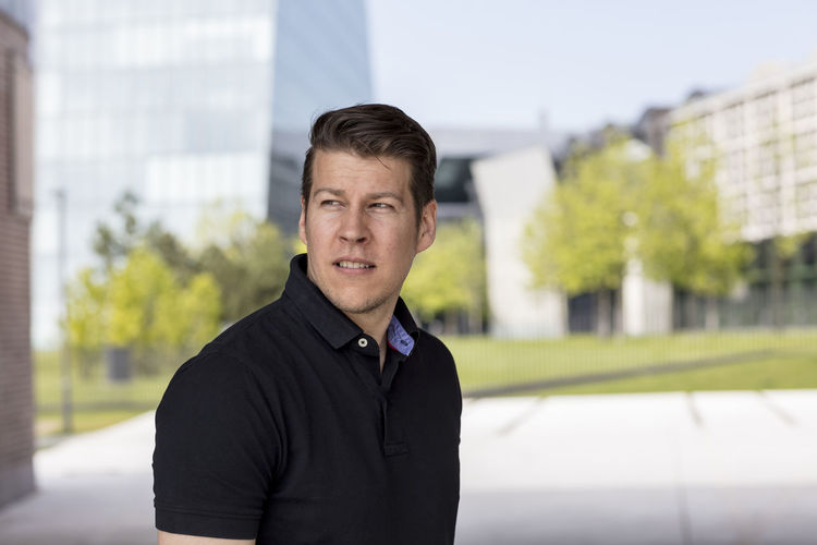 Casually dressed man wearing a golf shirt posing for the camera with an urban office setting in the background. Medium close up. Adult Afternoon Black Shirt City Life Front Facing Man Standing Sunny Trees Caucasian Ethnicity Causal Clothing Day Face Golf Shirt Haircut Handsome Male Medium Close Up Model Pose Office Building Posing Relaxed Sky Summer Urban