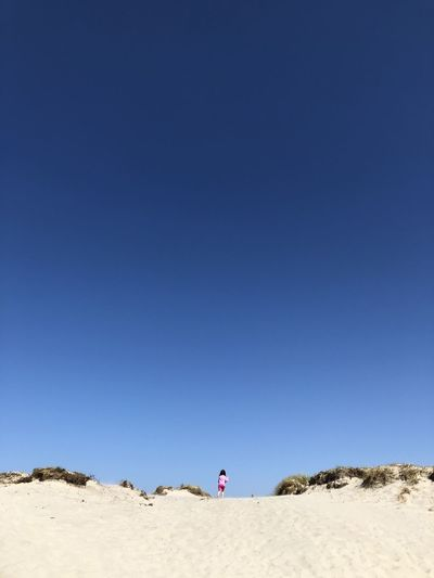 Woman on shore against clear blue sky