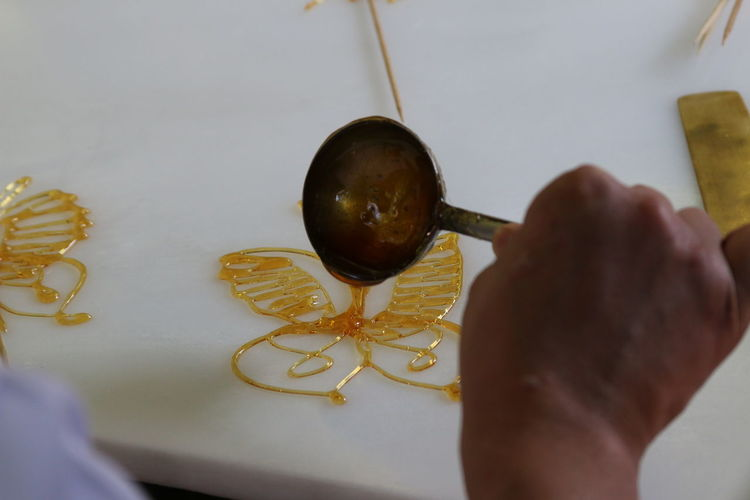 Cropped Image Of Hand Making Caramel Decoration On White Table