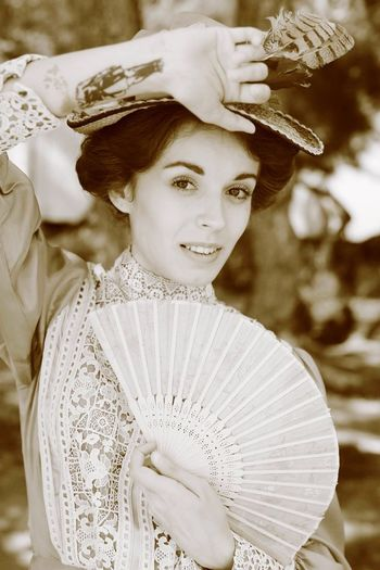 Portrait of beautiful young woman holding folding fan